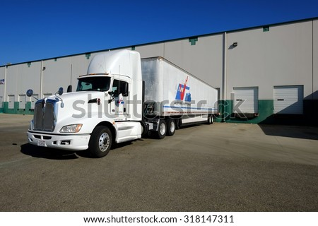 SHAFTER, CA - SEPTEMBER 17, 2015: This large industrial warehouse complex is a transportation hub for Central California. A tractor trailer rig unloads its cargo at the loading dock.