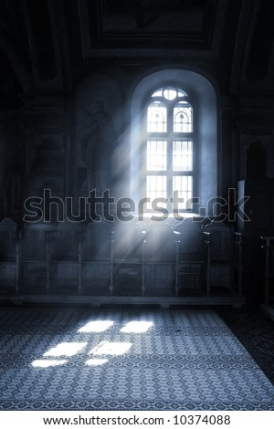 Shafts of light stream through stained glass window inside a church