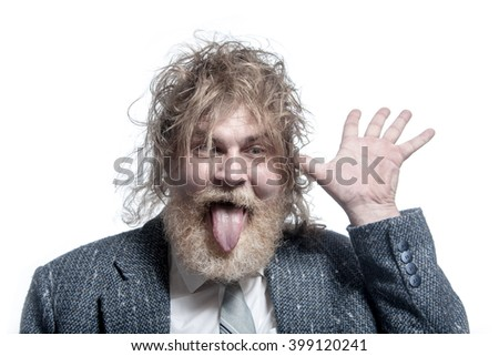 Shaggy adult gray-haired man with a beard wearing a gray suit shows tongue and holds a hand near the ear. Isolated - stock photo