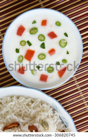 Shai Pulao or Vegetable Pulao or Indian Biryani or Pilaf or fried rice made of  Basmati rice in a white bowl served along with curd or raita on bamboo mat.a dish in Asia India,the Middle East - stock photo