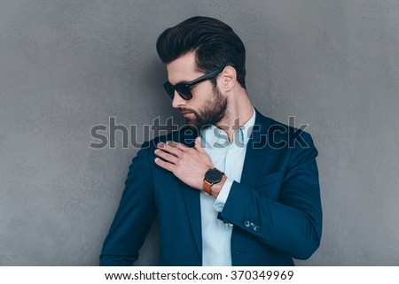 Shake it off. Close-up of young handsome man in sunglasses shaking off invisible dust from his shoulder while standing against grey background - stock photo