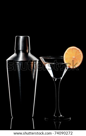 Shaker and cocktail in martini glass on a black background