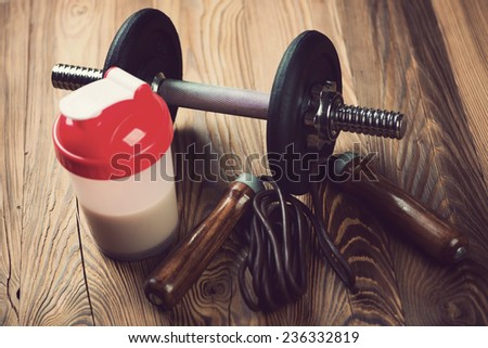 Shaker with protein, a jumping rope and a dumbbell, close-up - stock photo