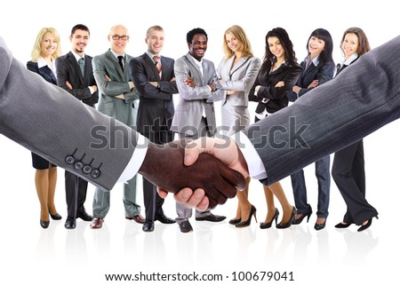 shaking hands and business team formed of young businesspeople - stock photo