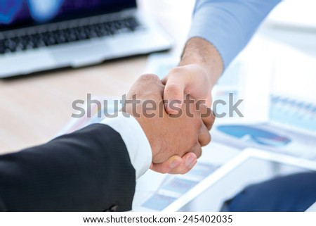 Shaking hands at a meeting. Two Confident businessman sitting at the negotiating table in the office and shaking hands close-up view of hands. Business people dressed in formal wear - stock photo