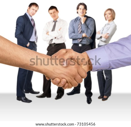 Shaking hands of two businessmen against four businesspeople standing in the background - stock photo