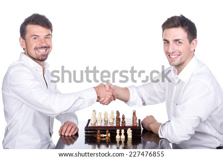 Shaking hands of two men are playing chess on the white background. - stock photo