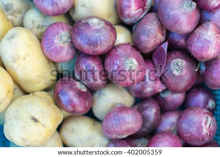 Shallot or Onions and yam in blue basket at market