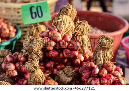 Shallots clusters in a plastic box as sold on market.Red giant shallot,base ingredient for Thai spicy food. - stock photo