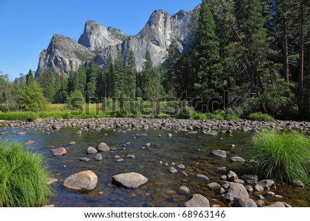Shallow channel Merced River, covered with stones, in the famous Yosemite Park - stock photo