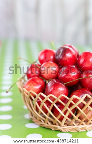 Shallow depth cherries in the basket blurred background