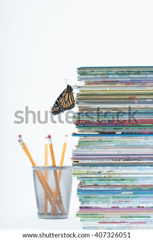 Shallow depth of field catches one monarch butterfly climbing up a pile of children's story books. A finishing touch with pencils faded out in the white background. Vertical with copy space. - stock photo