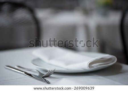 Shallow depth of field close up of knife, fork, plate and folded napkin laid upon white table cloth at elegant restaurant.    - stock photo