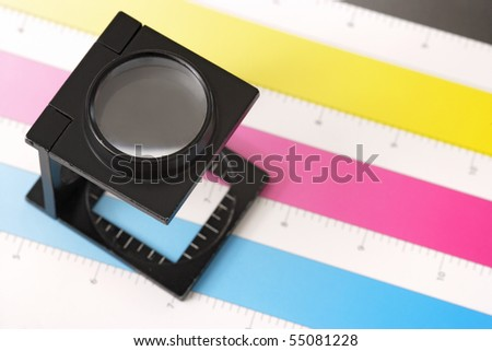Shallow depth of field image of a printers loupe on printed sheet.  Focus is on the top of the loupe. - stock photo