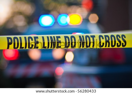 Shallow depth of field image taken of yellow law enforcement line with police car and lights in the background. - stock photo
