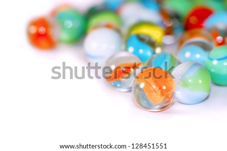 Shallow depth of field on scattered, colorful marbles. Selective focus adds to copy space.  Orange and blue are prominent colors with yellow and green.  Marbles are shiny glass spheres used in games - stock photo