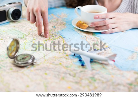 Shallow depth of field. woman sitting at table with a map with a paper airplane, compass and camera and visualises his desire to travel - stock photo
