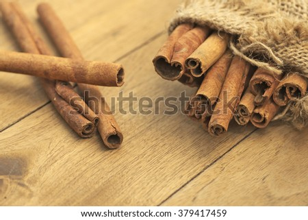 Shallow DOF closeup of cinnamon barks over rustic wooden table - stock photo