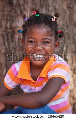 shallow DOF of african child with braids and orange dress - stock photo
