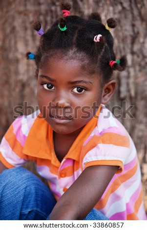 shallow DOF of african child with braids and orange thirt - stock photo