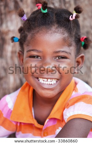 shallow DOF of African child with braids and orange tshirt - stock photo