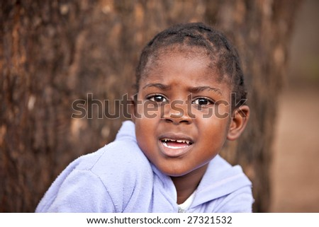 shallow DOF of scared african child , bark of tree background - stock photo