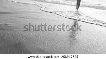 Shallow focus on sand with a woman's feet walking along the beach in the waves in black and white - stock photo