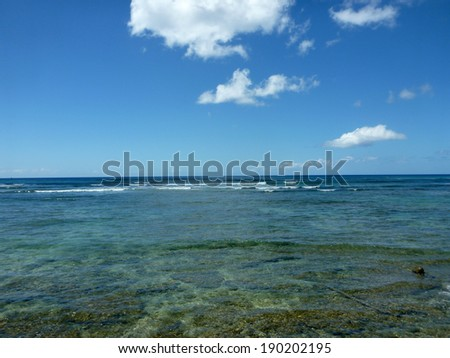 Shallow ocean waters with coral and small waves breaking in the distance of Waikiki area looking into the pacific ocean. - stock photo