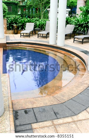 Shallow paddling pool for children with sun loungers around perimeter