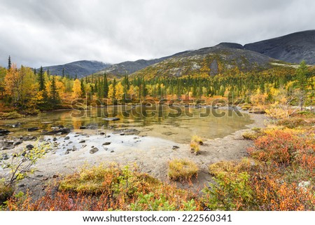 Shallow Polygonal lake surrounded by greenery with mountain ridge reflection - stock photo