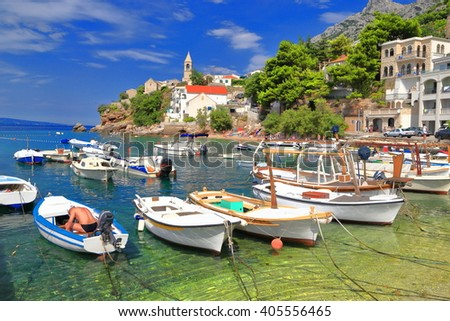 Shallow water and traditional bots on Dalmatian coast harbor, Croatia - stock photo