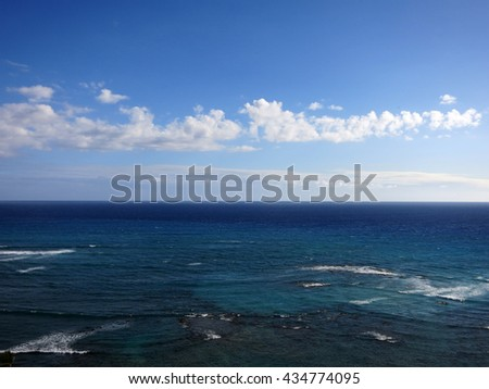 Shallow wavy ocean waters of Waikiki looking into the pacific ocean with blue sky and clouds on Oahu. - stock photo
