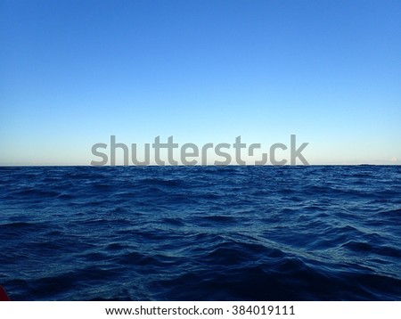 Shallow wavy ocean waters of Waimanalo bay looking into the pacific ocean with a clear blue sky on Oahu. - stock photo