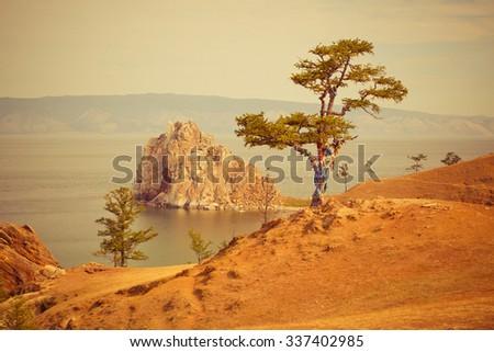 Shaman rock Lake Baikal in the summer in a yellow filter - stock photo