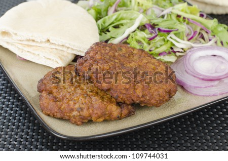 Shami Kebabs - A couple of spicy lamb kebab patties served with crunchy salad, pitta bread and raw red onions. - stock photo