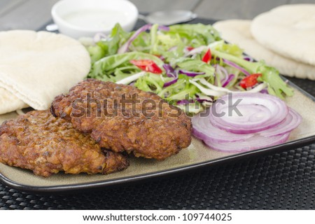 Shami Kebabs - A couple of spicy lamb kebab patties served with mint raita dip, crunchy salad, pitta bread and raw red onions. - stock photo