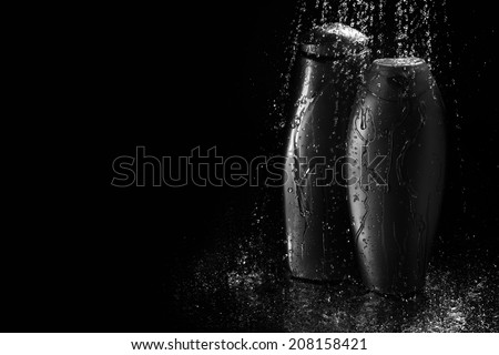 shampoo and gel bottles in falling drops of water on black background - stock photo