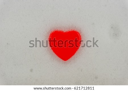 Shampoo foam is a red heart. Heart on the foam from the shampoo background.