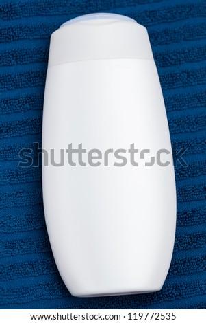 shampoo on blue towel - stock photo