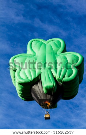 Shamrock shaped green hot air balloon against bright blue morning sky just after take off - stock photo