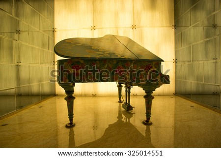 SHANGHAI, CHINA, APRIL 2: A decorated piano in yellow light installed in the hall of a hotel in Shanghai. China 2013 - stock photo