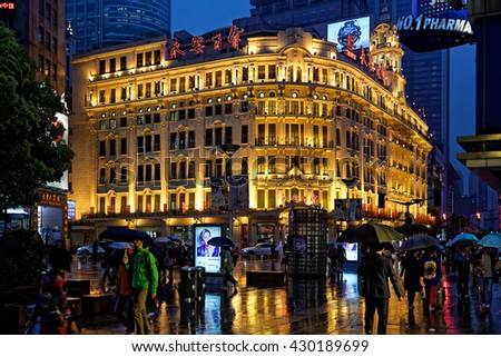 SHANGHAI, CHINA - April 20, 2016:  Nanjing Road with people and colorful signboards glowing at rainy night. - stock photo