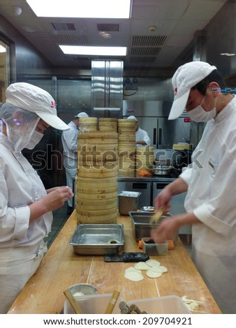 SHANGHAI, CHINA, APRIL 12: Two unidentified chefs at work in a Chinese restaurant kitchen in Shanghai on 12 April 2013. - stock photo