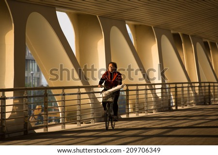 SHANGHAI, CHINA, APRIL 11: unidentified woman cycling under a bridge with french bread saying bon matin Paris, Shanghai 11 April 2013.