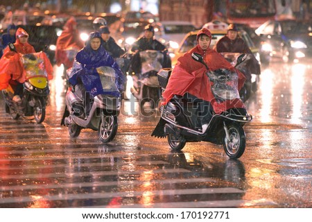 SHANGHAI, CHINA - JUNE 17: Crossroad in Shanghai in heavy rainy night on June 17, 2012 in Shanghai. Scooters cross street near Zhongshan park, Changning district. Cars traffic in background. - stock photo