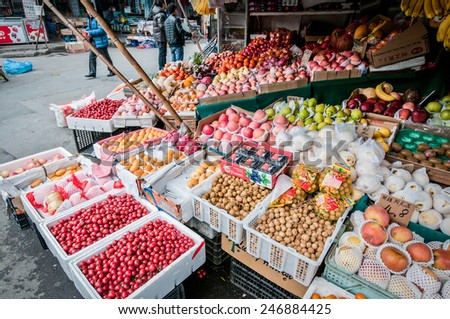 SHANGHAI, CHINA - MARCH 22: People passing next to greengrocery with vegetables and fruits at food market on March 22, 2013 in Old City of Shanghai (Nanshi)