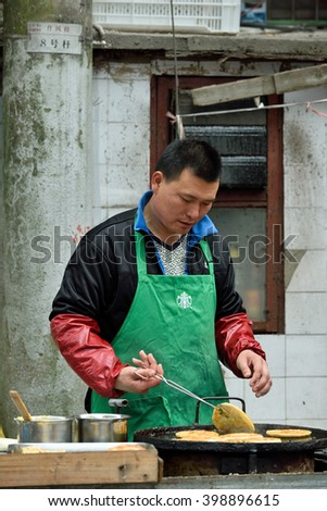 SHANGHAI, CHINA - MARCH 19: Unidentified Chinese people trades traditional food on March 19, 2016 in Shanghai, China. Shanghai is the largest Chinese city by population. - stock photo