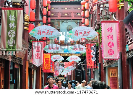 SHANGHAI, CHINA - MAY 30: Chenghuangmiao street with crowded stores and decorations on May 30, 2012 in Shanghai. It is the largest city by population in the world with 23 million in 2010