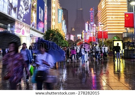 SHANGHAI, CHINA - MAY 2, 2015: Visitors and neon lights at Nanjing Road. It is the main shopping street of Shanghai, China, and is one of the world's busiest shopping streets.