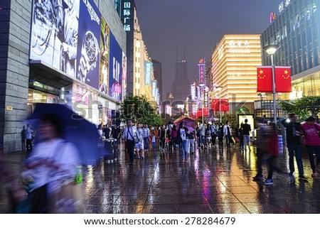 SHANGHAI, CHINA - MAY 2, 2015: Visitors at Nanjing Road during a rainy day at night. It is the main shopping street of Shanghai, China, and is one of the world's busiest shopping streets. - stock photo